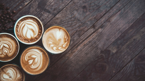 photo of a5 coffee cups in a row, on a wooden table, decorated with a froth art.